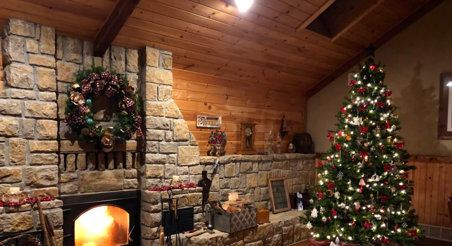 Stone fireplace with christmas wreath and Christmas tree in background