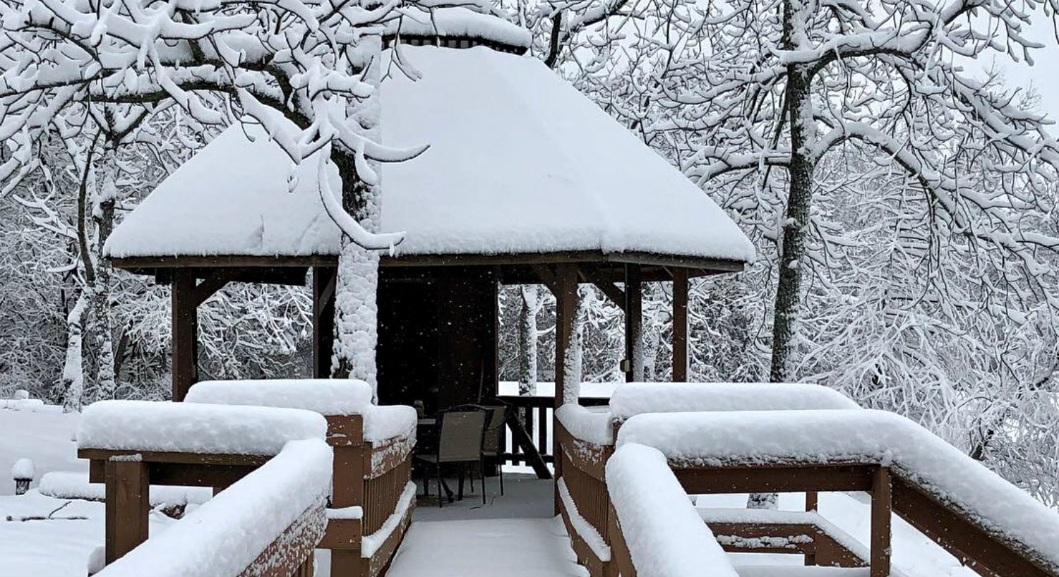Gazebo, pier and trees covered in fresh white snow