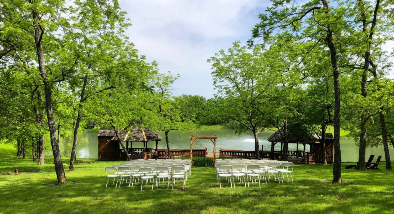 White chairs in rows in front of wedding arbor overlooking twin gazebos and pond