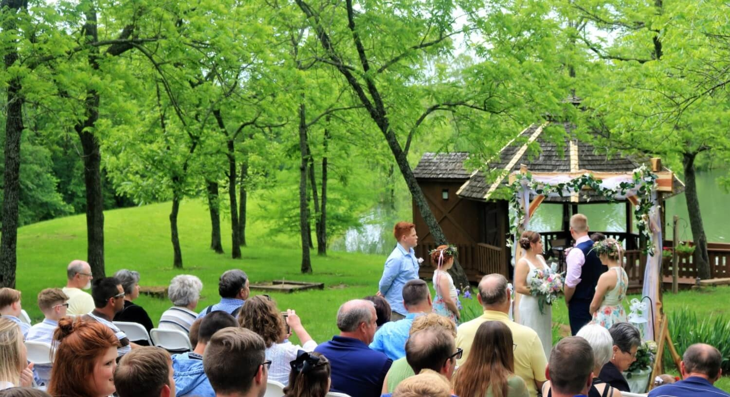outdoor wedding with guest watching couple say their vows by pond