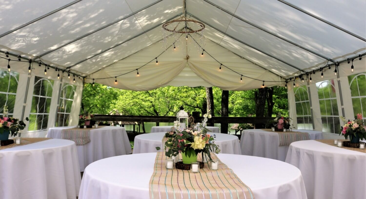 Inside of white wedding tent, tables with white linens, tan table runner and fresh flowers