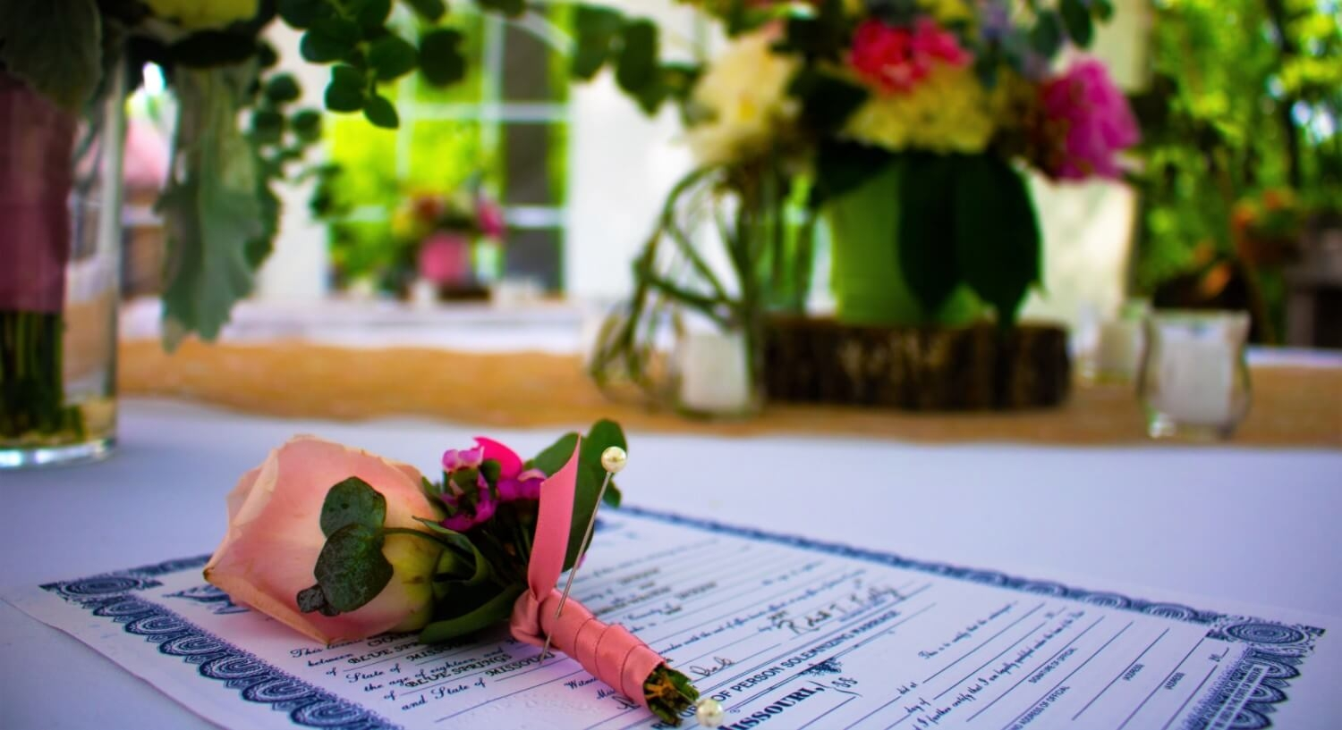 Wedding license on table with pink flower and  fresh flowers in background