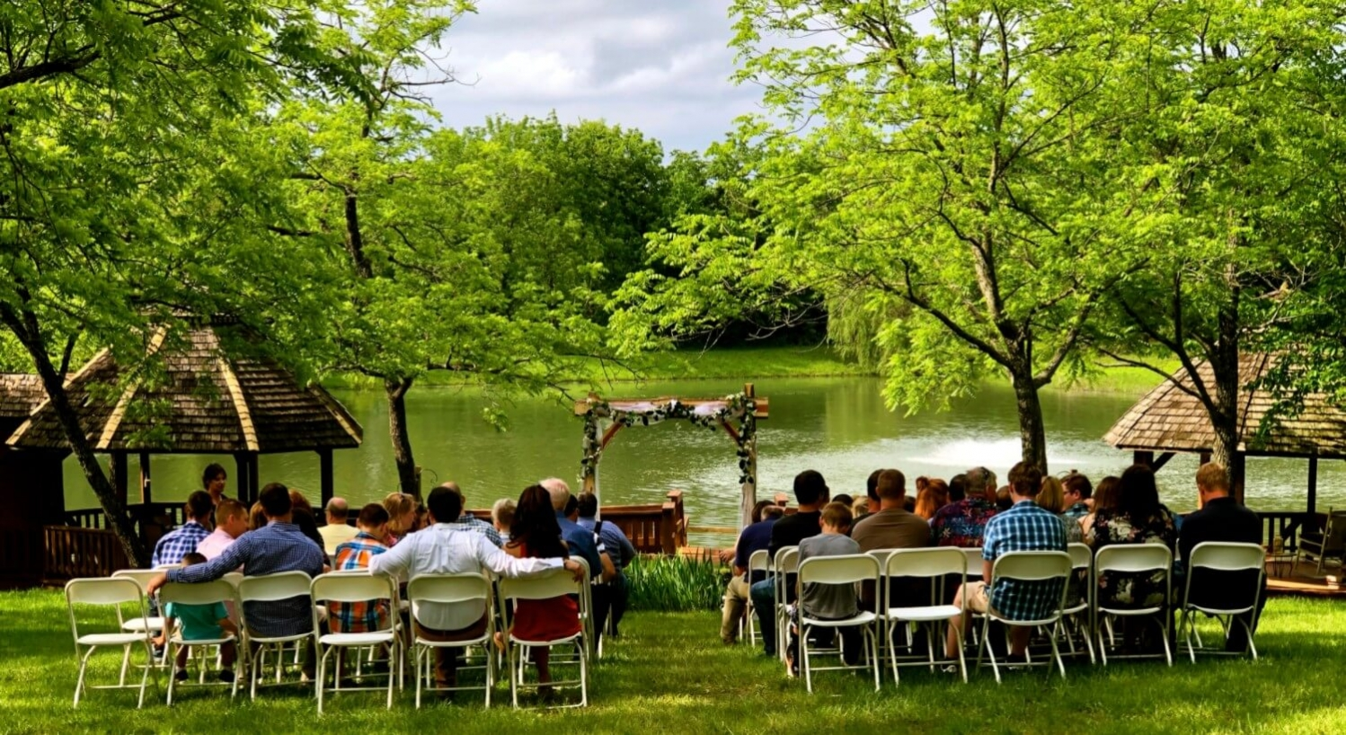 Outdoor wedding  with guest seated facing arbor and pond