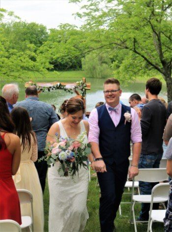 Outdoor wedding with bride and groom surrounded by guests