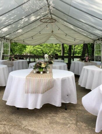 inside of white wedding tent, tables with white linens, tan runner and fresh flowers and candles