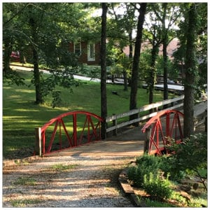 Wooded area with a red bridge next to a white wooden fence leading to a brown building