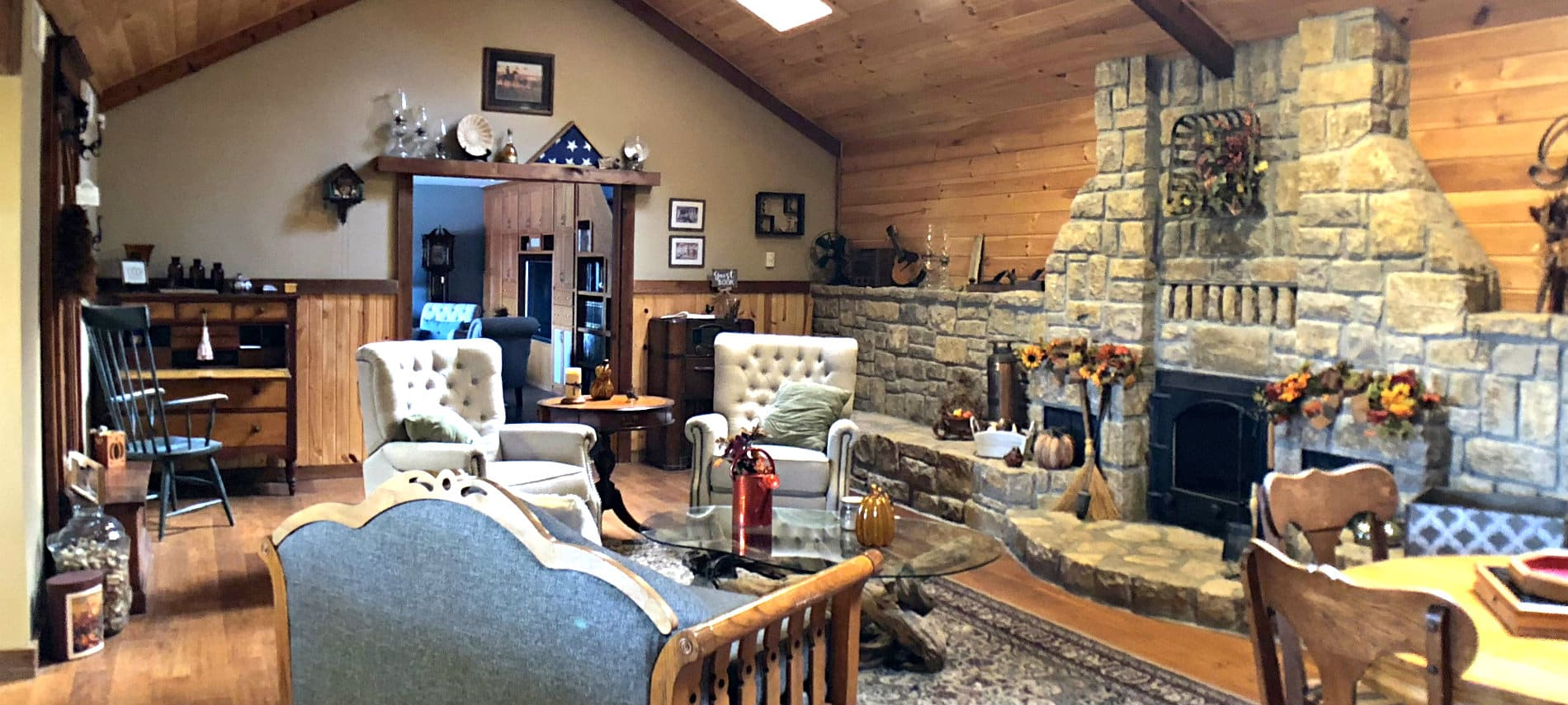 Large vaulted room with wood floors, stone fireplace, dining tables and upholstered chairs