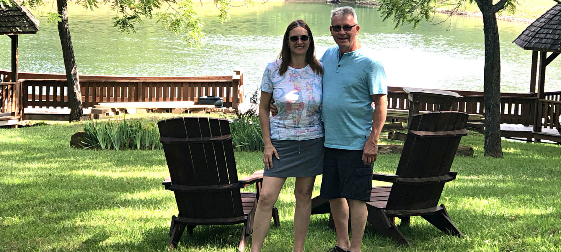 Innkeepers Karl and Rebecca standing by two lounge chairs in the lawn with the pond in the background