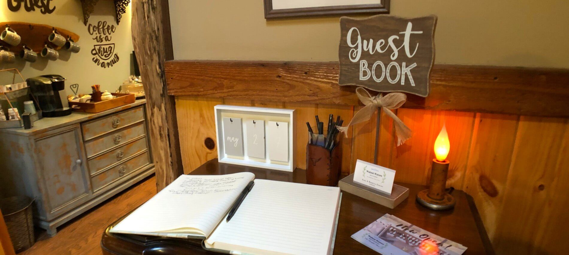 Open guest book lying on a dark wood table