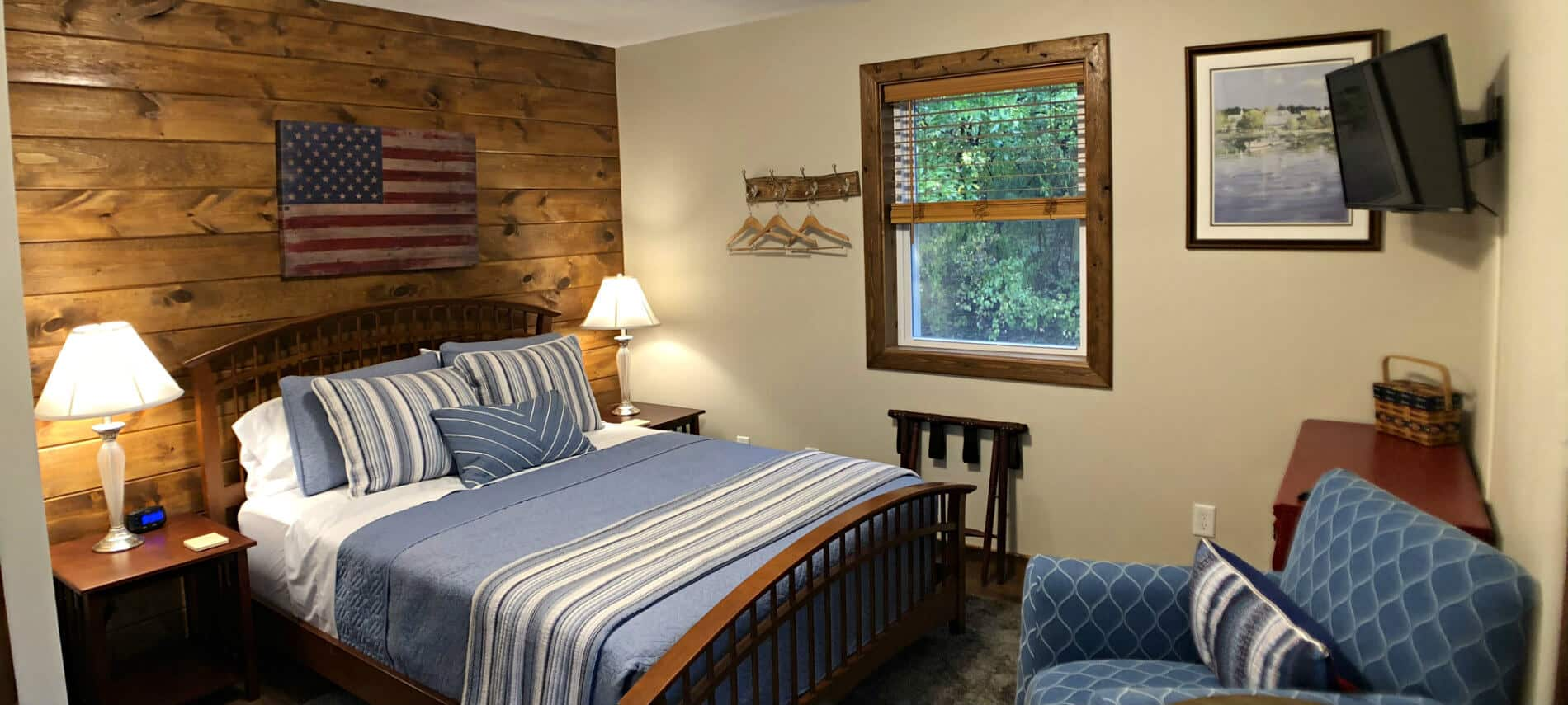 Sycamore guest room with plank wall, blue bedding and chair, nightstands, TV and small window