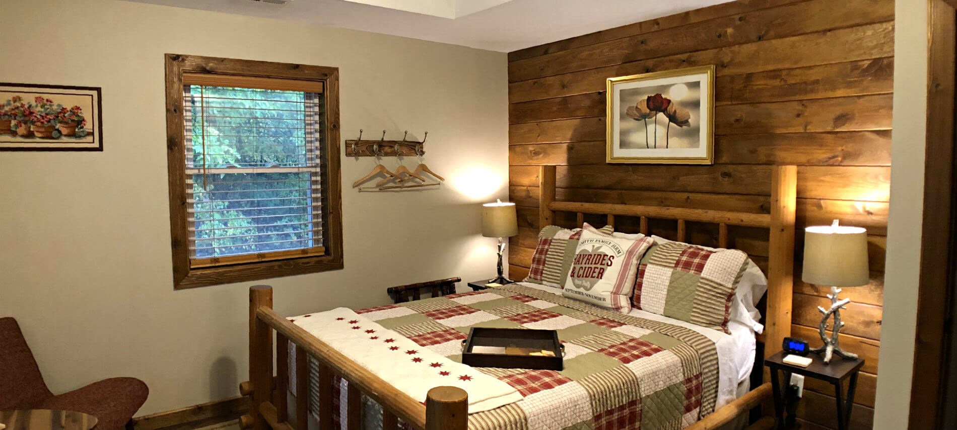 Willow guest room with a plank wall, rustic bed with plaid quilt, and small window