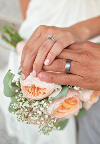 Bride and grooms hands wearing wedding rings resting on a bouquet of peach and white flowers