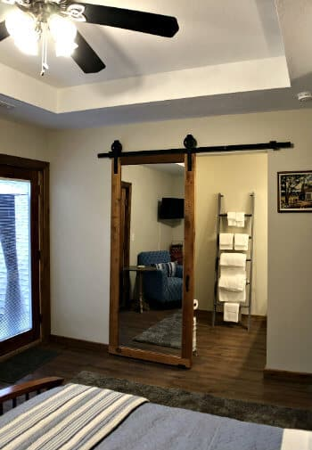Rustic mirrored barn door leading to attached bath in the Sycamore guest room