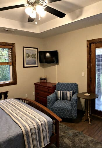 Sycamore guest room with tray ceiling, ceiling fan, French door, blue chair, and TV