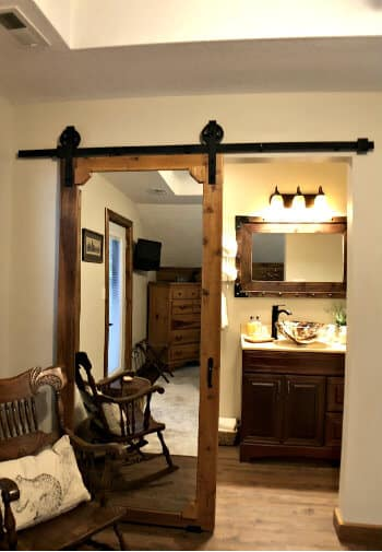 Rustic mirrored barn door leading to attached bath in the Walnut guest rom