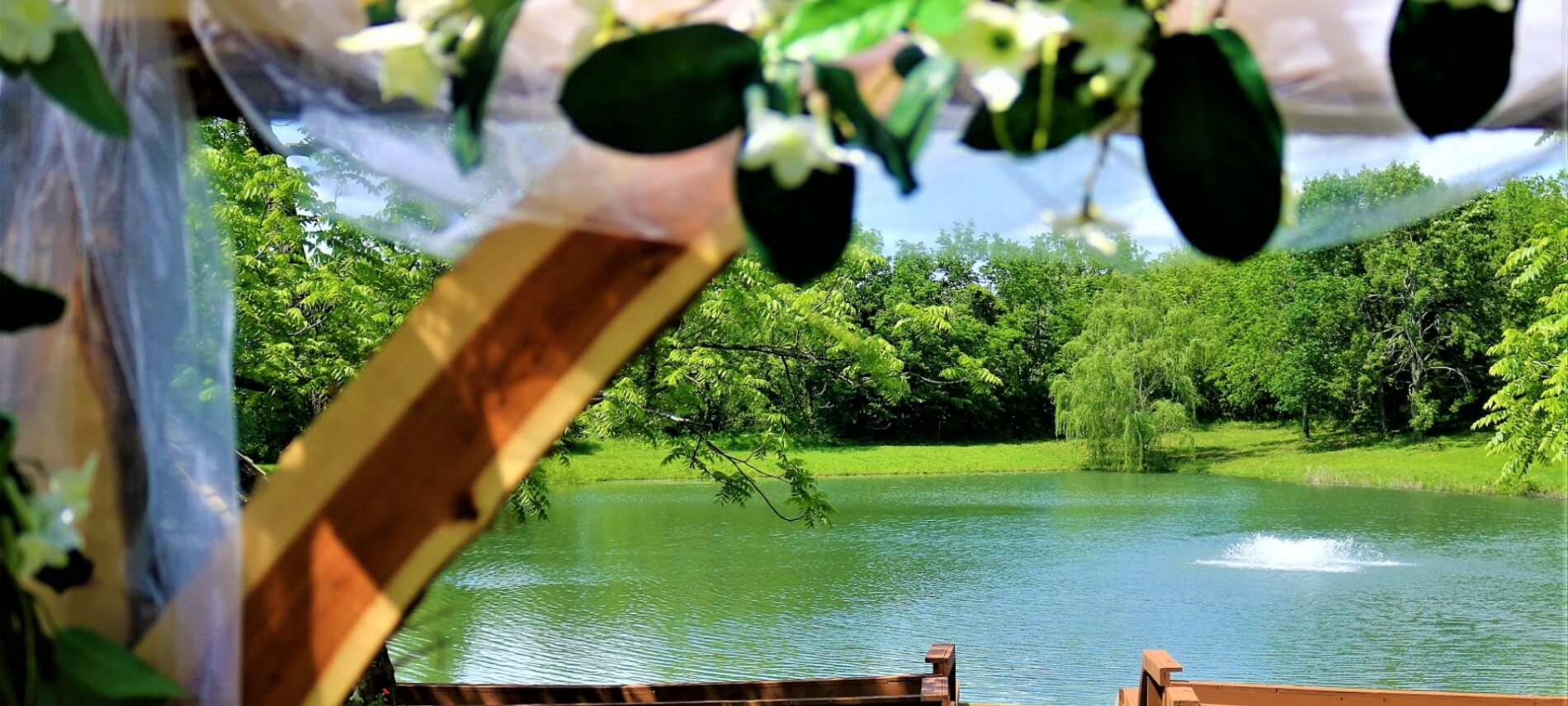 View of pond through woodend wedding arbor with white flowers and greenery