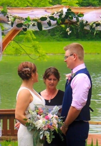 Outdoor wedding bride and groom exchanging vows under a wooden arbor with pond in background