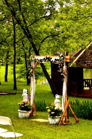 outdoor wooden wedding arbor decorated with white flowers, greenery and white fabric,